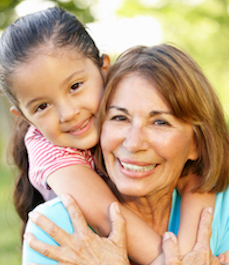 Hispanic Grandmother And Granddaughter Relaxing In Park